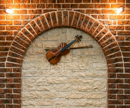 wall sconce: Element of the interior stone arch with a violin on a wall Stock Photo