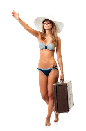 Full length portrait of a beautiful young woman posing in a bikini, hat and sunglasses with a suitcase in hand on white background photo