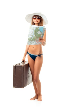 Full length portrait of a beautiful young woman posing in a bikini, hat and sunglasses with a suitcase and map in hands on white background photo