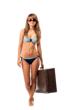 Full length portrait of a beautiful young woman posing in a bikini and sunglasses with a suitcase in hand on white background photo