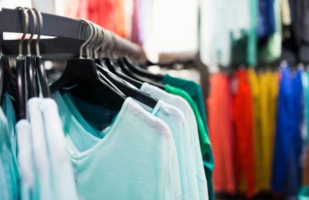 tienda de ropas: Ropa de colores de moda en perchas en la tienda Foto de archivo
