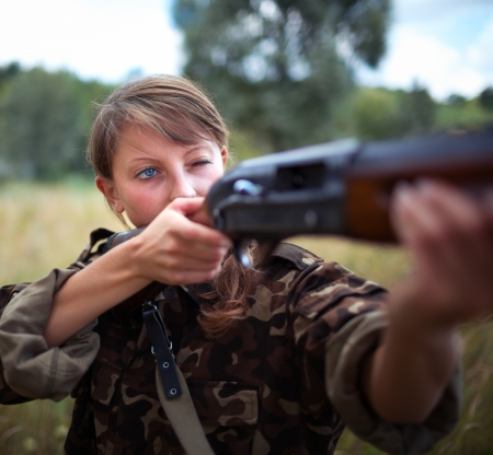 A young girl with a gun aiming at a target photo