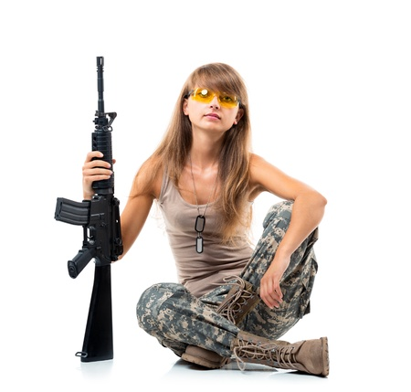 Soldier young beautyful girl dressed in a camouflage with a gun in his hand on white background Stock Photo - 21467498