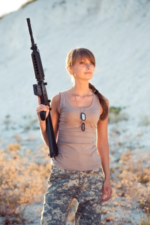 Young beautiful female soldier dressed in a camouflage with a gun in the outdoor photo