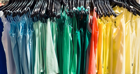 Fashionable colorful clothes on hangers in the store photo