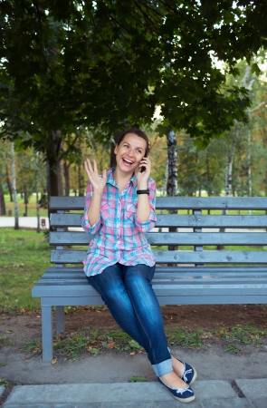 A portrait of a smiling beautiful woman in a park on a bench talking on the phone photo