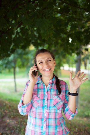 Portrait of a smiling young woman in a park talking on the phone photo
