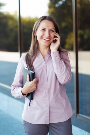 Young businesswoman with cellphone and organizer while standing against office building, outdoor
