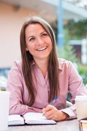 Smiling businesswoman sitting in a cafe and writing in notepad photo