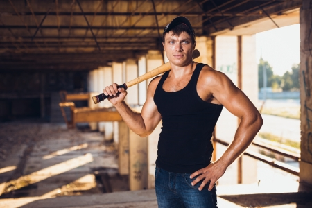 Muscular man with baseball bat on the ruins photo