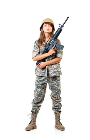 Soldier young beautiful girl dressed in a camouflage with a gun in his hand on white background photo