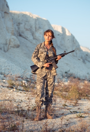 Young beautiful female soldier dressed in a camouflage with a gun in the location photo