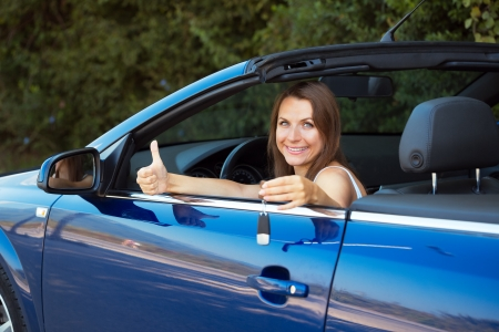 Smiling caucasian woman showing key in a cabriolet car photo