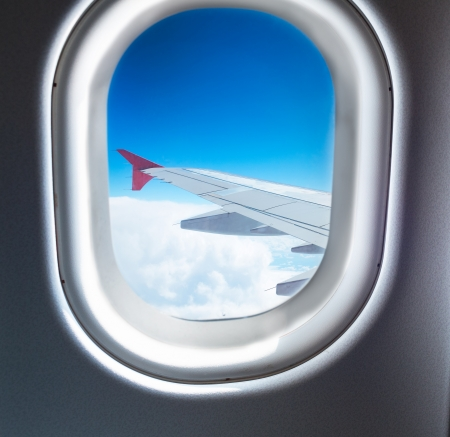 Airplane window where you can see the wing which flies above the clouds photo
