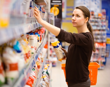 Beautiful young woman shopping for cereal, bulk in a grocery supermarket photo
