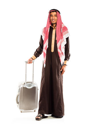 Young smiling arab with a suitcase isolated on white background photo