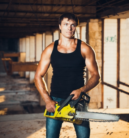 Muscular man with a chainsaw on the ruins photo