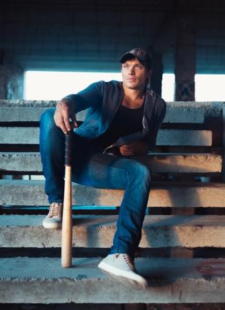 Muscular man with baseball bat on the ruins photo