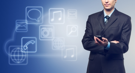 Businessman with touch screen phone and the cloud with applications icons on blue background photo