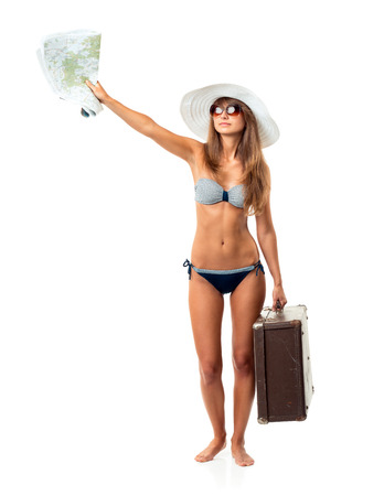 Full length portrait of a beautiful young woman posing in a bikini, hat and sunglasses with a suitcase and map in hands on white  photo