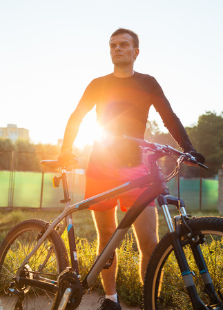 Mountain bike cyclist riding at sunrise healthy lifestyle active athlete doing sport photo
