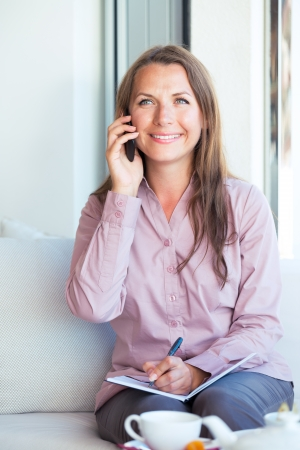 Happy businesswoman talking on the phone and writing in organizer in a coffee shop Stock Photo - 25254177