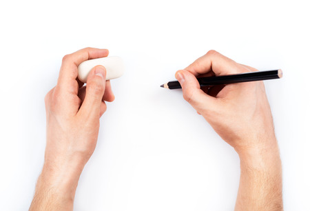Human hands with pencil and erase rubber writing something. Stock Photo - 25254204