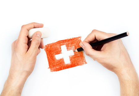 Mans hands with pencil draws flag of Switzerland on white background photo