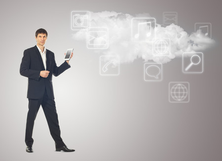 Businessman with tablet and the cloud with applications icons on grey background photo