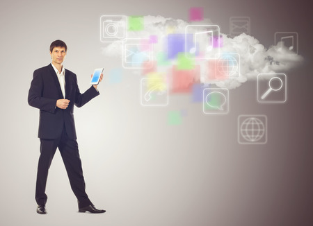 Businessman with tablet and the cloud with applications icons on grey  photo