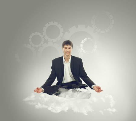 Businessman sitting in lotus position on a cloud and think mechanical thoughts photo