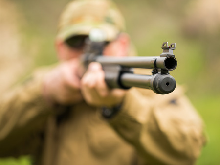 Man in camouflage with a shotgun aiming at a target. Focus on tvole, small DOF photo