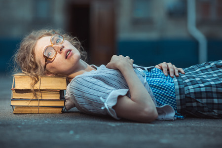 Funny crazy girl student with glasses lying on a pile of books outdoor photo