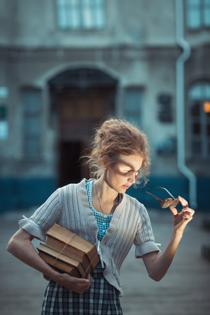 Funny girl student with glasses and a vintage dress outdoors photo