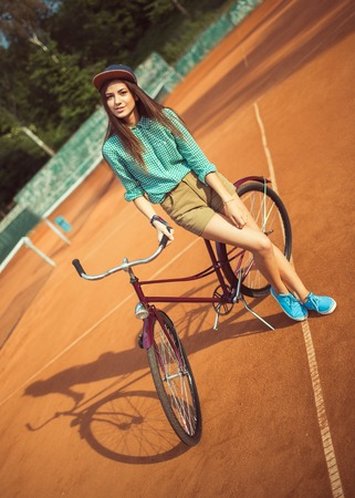 Girl hipster standing with magenta bike on the tennis court. Outdoor lifestyle portrait photo