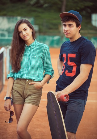 Young beautiful couple standing on a skateboard on the tennis court photo