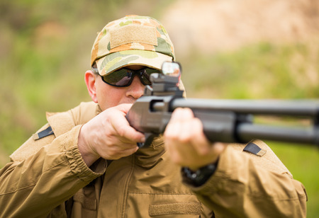 sniper training: Man in camouflage with a shotgun aiming at a target