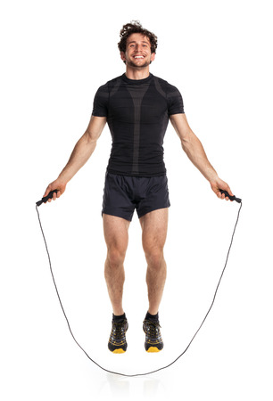 Athletic attractive man jumping on a rope on the white background photo