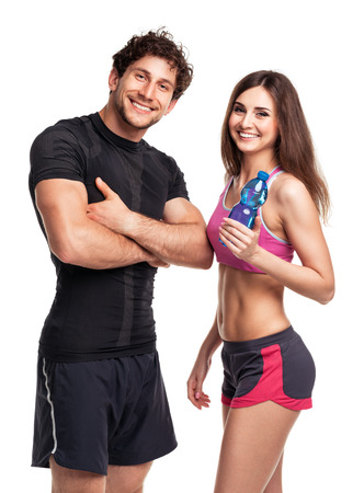 Athletic couple - man and woman with bottle of water on the white background Stock Photo