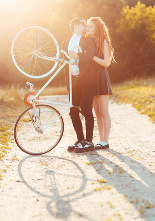 Young stylish couple - the guy with the girl and bicycle outdoors photo