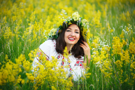 maidan: Young beautiful smiling girl in Ukrainian costume with a wreath on his head in a meadow
