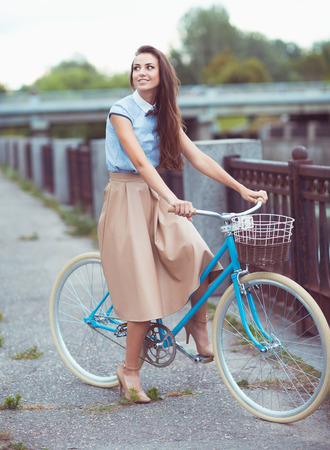Young beautiful, elegantly dressed woman with bicycle. Beauty, fashion and lifestyle photo