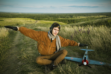 Young guy in vintage clothes pilot with an airplane model outdoors photo