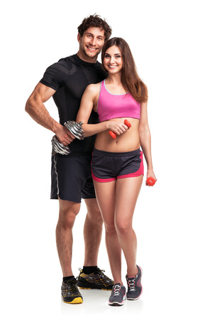 Athletic couple - man and woman with dumbbells on the white background photo
