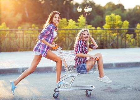 gente loca: Dos felices hermosas chicas adolescentes conduciendo carro de compras al aire libre, estilo de vida concepto Foto de archivo