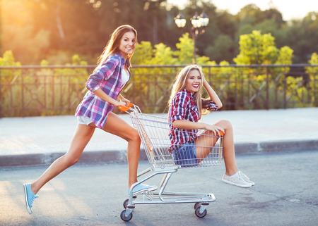 Two happy beautiful teen girls driving shopping cart outdoors, lifestyle concept