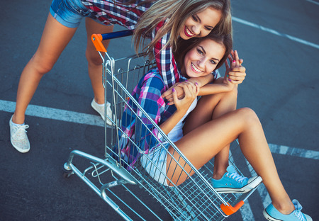 Two happy beautiful teen girls driving shopping cart outdoors, lifestyle concept photo