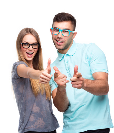two thumbs up: Happy couple smiling holding thumb up gesture, beautiful young man and woman smile looking at camera on white Stock Photo