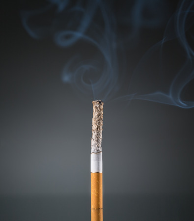 Smoking cigarette on black background photo