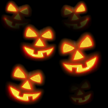 Lots of pumpkins lit brightly against a black background photo